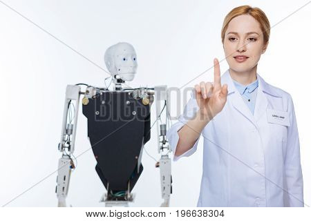 Using the finger. Enthusiastic dedicated industrious woman using interactive computer and pushing the start button while programming the robot in a lab