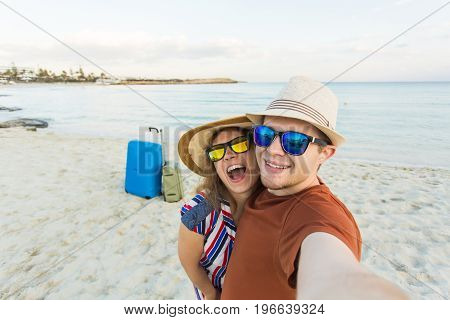 Happy traveling couple in love taking a selfie on phone at the beach on a sunny summer day. Pretty girl and her handsome boyfriend having fun, crazy emotional faces , laughing