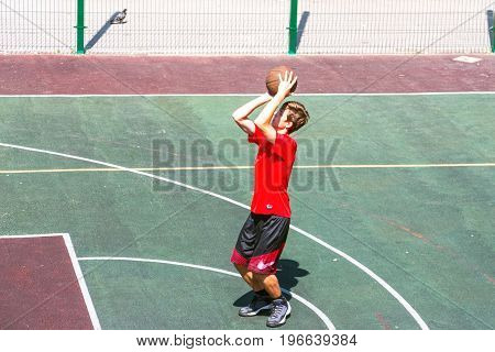 SAMARA, RUSSIA - JULY 14, 2017: A boy on the basketball court throws the ball.