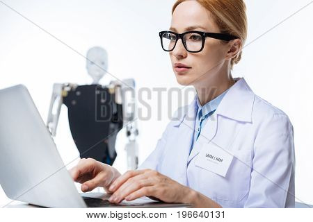 Ambitious project. Diligent productive incredible woman working on a scientific paper while sitting in a lab and analyzing empiric data