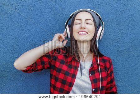 Portrait of happy hipster girl listening music in headphones. Technology, music, lifestyle and millennial people concept