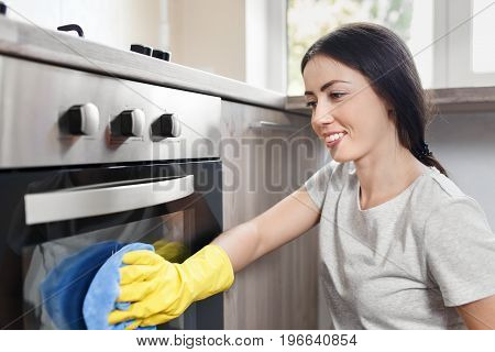 happy caucasian woman in protective glove with rag cleaning oven. Girl polishing kitchen. People, housework, housekeeping, cleaning concept
