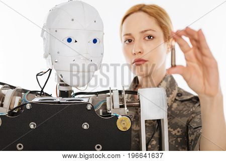Teaching the machine. Young serious progressive woman developing new weapon in the lab while creating artificial intelligence for combat purposes