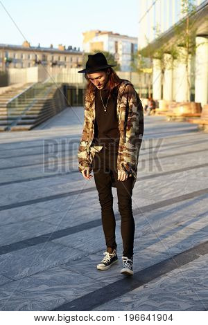 Stylishly dressed young European man standing in urban setting waiting for his girlfriend for walk. Full lenght portrait of hipster wearing trendy hat camouflage jacket and sneakers posing outdoors