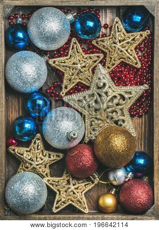 Christmas tree glittering toy stars, colorful balls and garland in wooden box, top view, vertical composition