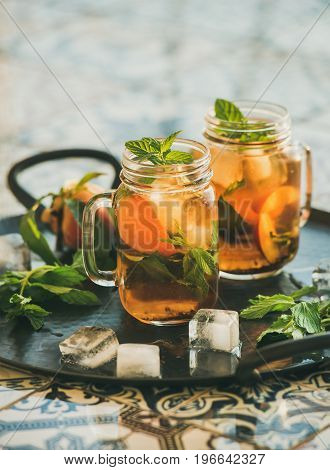 Summer refreshing cold peach ice tea with fresh mint in glass jars on metal tray over oriental ceramic tile background, selective focus, copy space