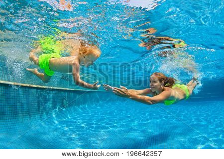 Happy family - mother baby son learn to swim. Girl dive in swimming pool with fun - jump underwater with splashes. Lifestyle summer children water sports activity swimming lessons with parent.