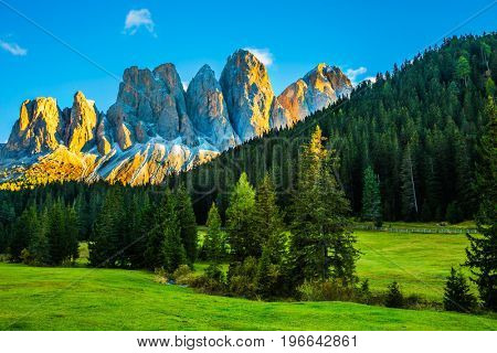 Magnificent serrated cliffs illuminate the summer sunset. The Dolomites, Tirol. The concept of eco-tourism in Alpine meadows