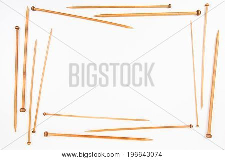 Frame of wooden bamboo knitting needles on white background. Top view