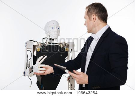 Another checkup. Devoted clever ambitious man using his gadget for giving the order to a robot while running some experiments in a lab