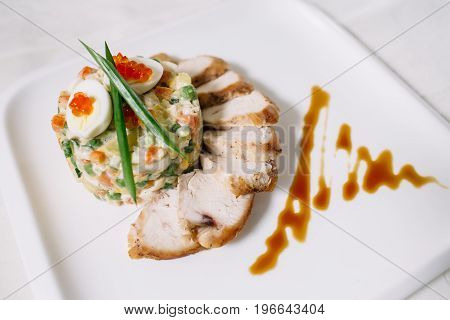 closeup of juicy grilled chicken fillet, white plates. Studio light