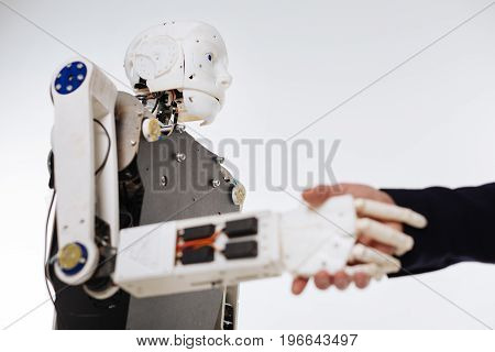 Polite machine. Scrupulous savvy devoted scientist checking the response system of elaborate machine while developing software for artificial intelligence