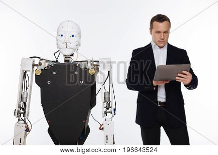 Double control. Attentive incredible focused man standing isolated on white background and holding a tablet while the robot standing in front of him