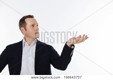 Big object. Concentrated diligent classy man pretending demonstrating something while looking at it and standing isolated on white background