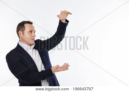 Showing the height. Curious bright focused man standing isolated on white background while pretending showing something big