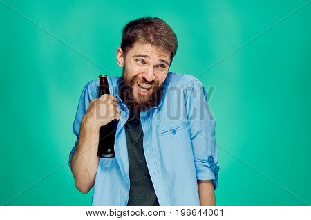 Man with a beard on a green background holds a bottle of beer, alcohol, drunk.