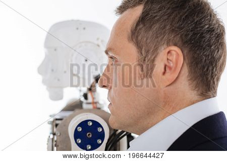 Facing the future in front of them. Handsome determined progressive scientist standing isolated on white background while posing with his invention for a photographer