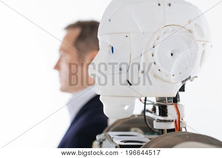 Resembling human. White progressive elaborate machine standing isolated on white background while posing with his invention during the photoshoot