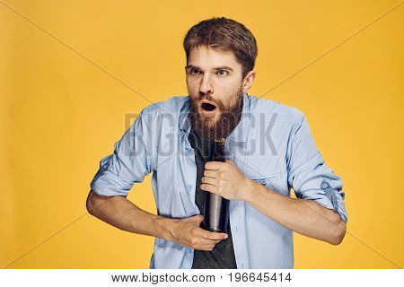 Man with a beard on a yellow background holds a bottle of beer, alcohol, drunk.