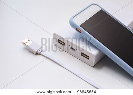Smartphone and power bank concept over grey