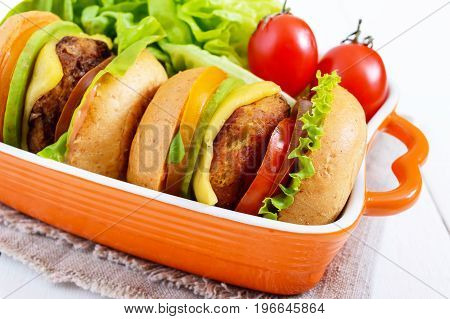 Sandwiches (burgers) with yellow and black tomatoes juicy cutlet avocado on a white wooden background. Close up