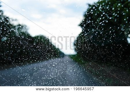 A view of the rainy weather through the windshield of a car that rides along the road. Drops in the foreground in focus. Traveling in bad weather.