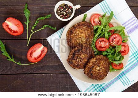 Juicy cutlets on a plate with a salad of tomatoes and arugula on a dark wooden background. Top view.