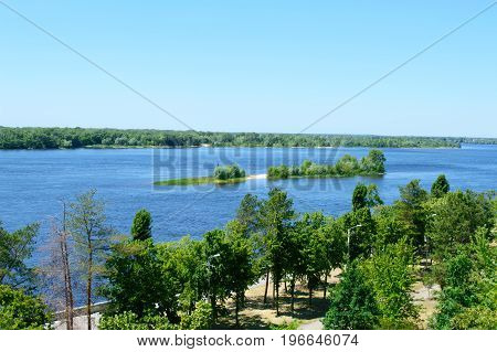 Beautiful landscape on a wide river with a small island green banks with a bird's-eye view. Sunny summer day.