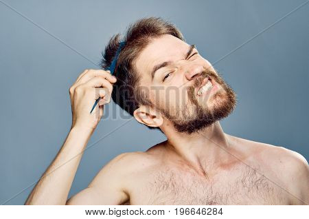 Man with a beard on a gray background combing.