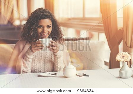 My favourite drink. Delighted attractive joyful woman holding a cup and smiling while enjoying her tea