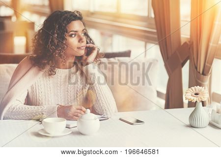 Sudden inspiration. Attractive dreamy young woman looking into the window and writing in her notebook while sitting in a cafe