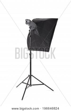 A professional softbox isolated over the white background. A dark black studio softbox on a long metal tripod. Photographic technique. Photographic equipment for professionals.
