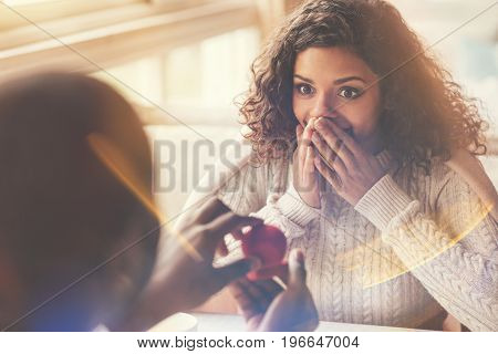 Taken by surprise. Delighted happy attractive woman sitting opposite her boyfriend and looking at the engagement ring while being surprised