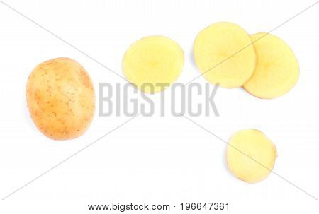 A top view of uncooked brown cut potatoes isolated on a white background. A whole potato and chopped round pieces full of nutritious starch. Autumn ingredients for vegetarian meals.