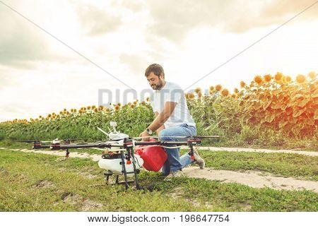 Young man pours fertilizer for irrigation in agriculture drone. Octocopter flight preparation. poster