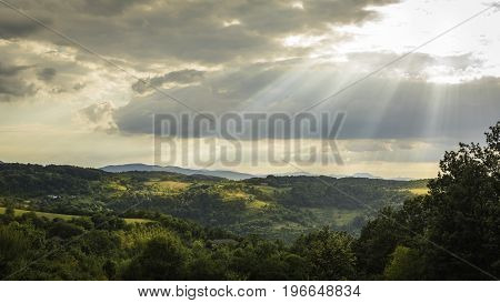 Mionica Serbia - July 24 2017: Landscape photo of hills of Mionica on a cloudy day with sun shining through clouds Mionica Serbia