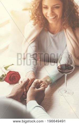 Romantic atmosphere. Happy delighted good looking couple sitting in the cafe and holding hands together while having a date