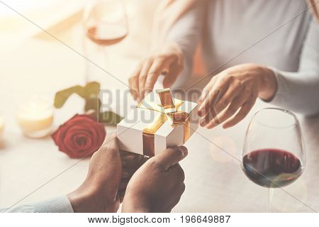 Present for you. Beautiful small gift being in hands of a handsome young caring man while being presented to his girlfriend