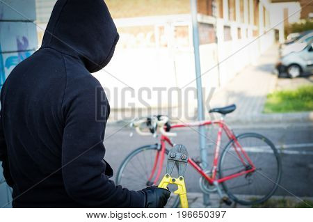 Thief Stealing A Parked Bike In City Street