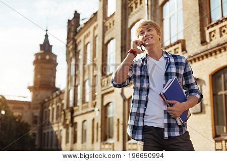 Nice hearing you. Handsome curious positive man enjoying a short break between classes and talking to his friend while heading to another lecture