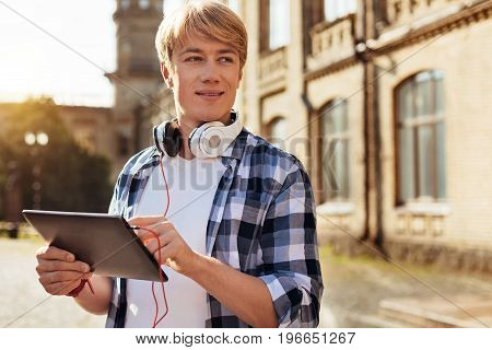 Walking outdoors. Enthusiastic cheerful nice man taking a moment between lectures and going outside while using his tablet