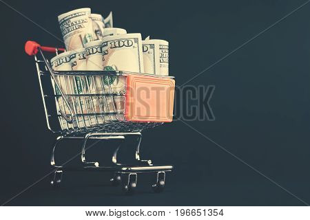 Shopping Cart Filled With One Hundred Dollar Bill Rolls.