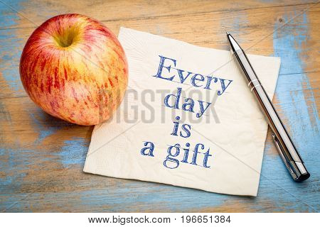 Every day is a gift inspirational reminder - handwriting on a napkin with a fresh apple