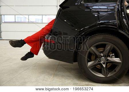 Car Mechanics Checking Up Pressure In Tires At Workshop