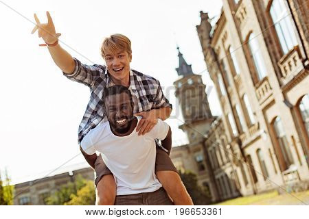 Like kids. Strong enthusiastic charming man giving his fellow student a ride while goofing around at the university and enjoying it