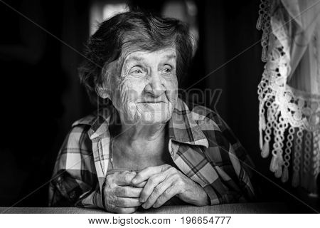 Portrait close-up of an elderly woman, in house by the window, a black-and-white photography.
