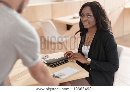 Beautiful Smiling African American Woman Paying With Cash In Cafe