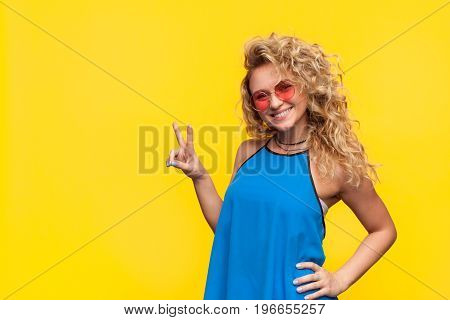 Charming curly woman in tank top and sunglasses showing two fingers and smiling at camera on yellow.
