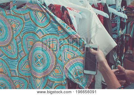 Woman selecting an apparel while shopping for clothes in a shop on Bali island, Indonesia. Shopping in Asia concept.