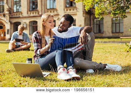Personal tutor. Sociable clever motivated girl helping her fellow student with the assignment while enjoying the warm day outdoors